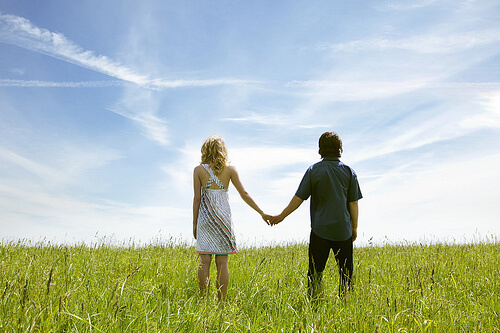 Couple holding hands in field, looking at horizon