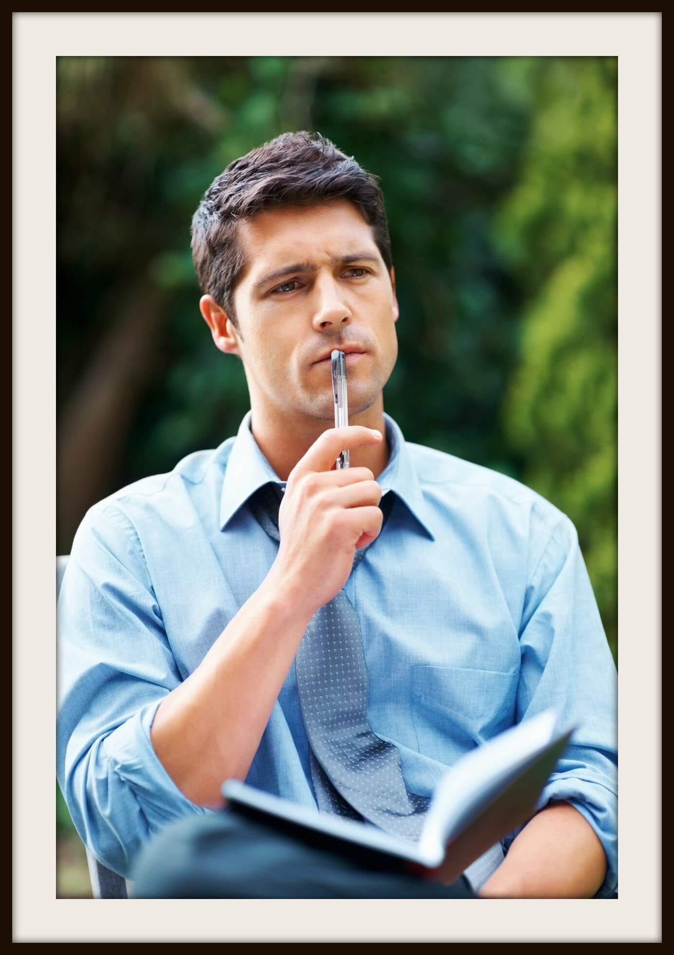 Business man sitting outdoors with book, looking into distance