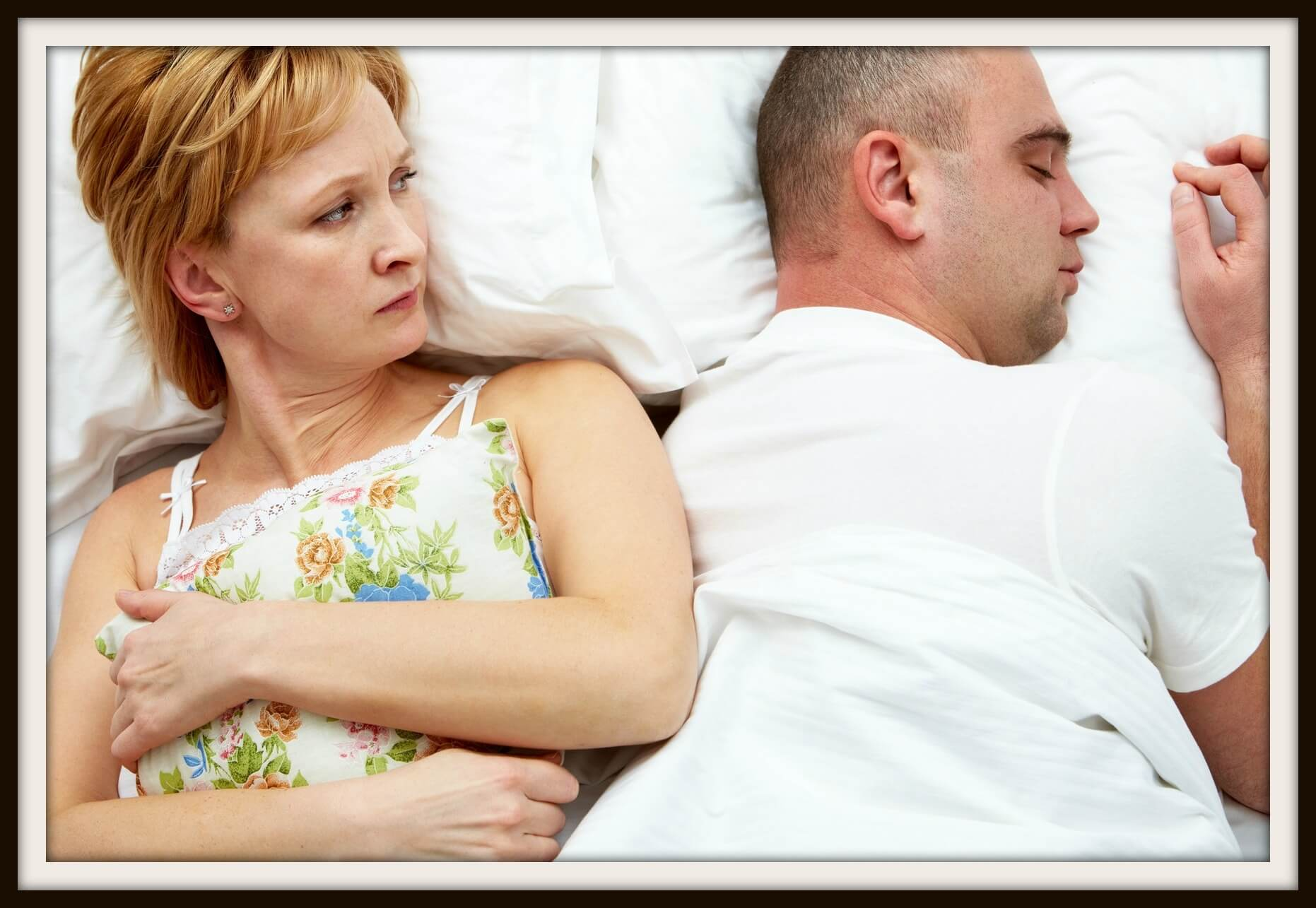 Photo of displeased wife holding pillow looking her husband