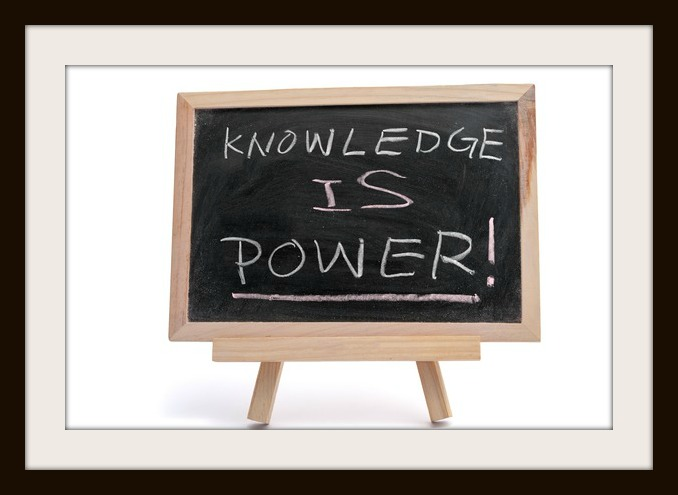 """Knowledge is power"" text written on blackboard over white background"