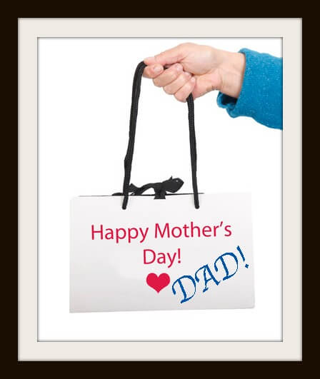 Hand in blue sweater holding white bag with ' Happy mother's day'  text