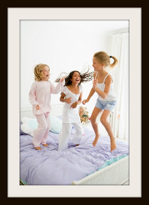 photodune-332349-three-young-girls-jumping-on-a-bed-in-their-pajamas-xs