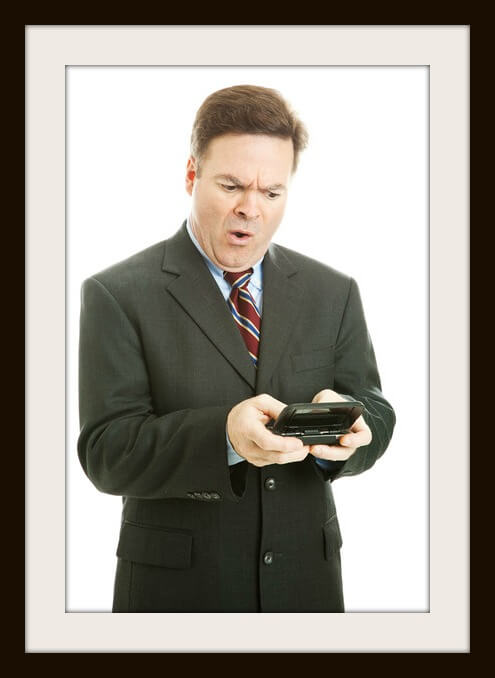 Fortiesh businessman offended by shocking text message.  Isolated on white.