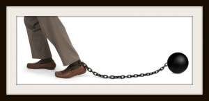 man's legs dragging a ball and chain