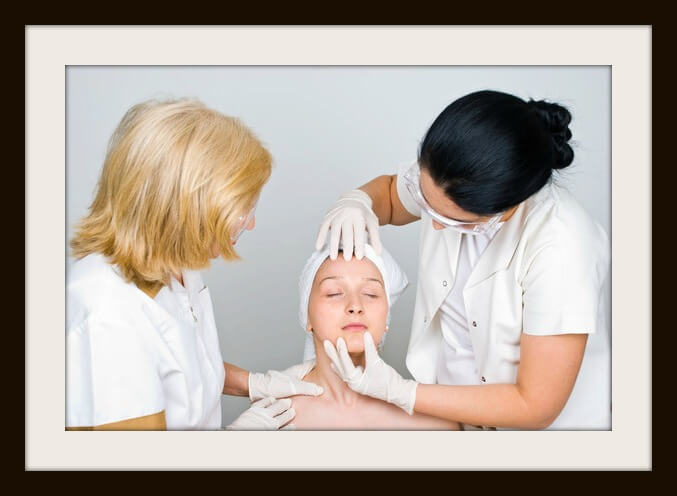 Two doctors examine woman face skin and preparing her for botox procedure