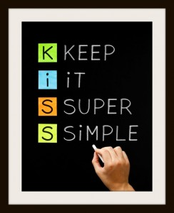 Hand writing Keep It Super Simple with white chalk on blackboard.