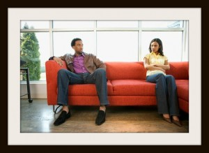 African American couple sitting on couch in dispute.