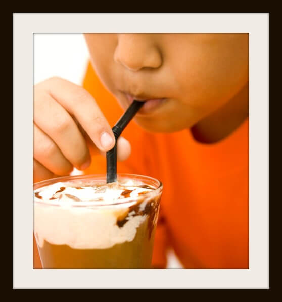 A kid wearing an orange shirt sipping a chocolate shake with a straw