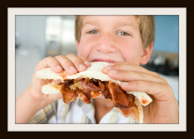 Boy eating bacon sndwich at home