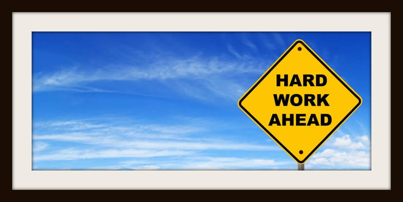 """Road sign warning of """"hard work ahead"""", against panoramic blue sky."""