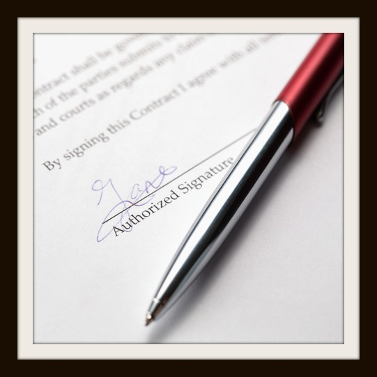 A stylish pen laying over a signed contract.