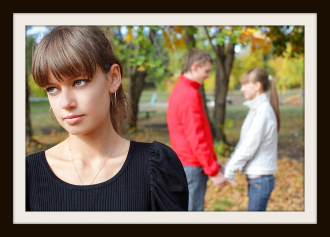 Sad young woman against happiness couple