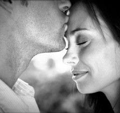 Portrait of young man kissing his pretty young  woman on forehead - outdoor