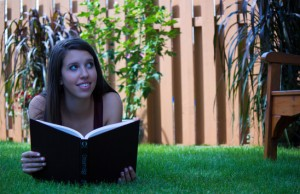 Pretty teen girl reading outside - copyspace