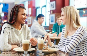 Image of two teenage girls eating cakes and talking in cafe