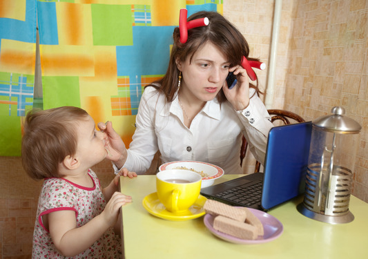 Mother feeding baby and  using  latop