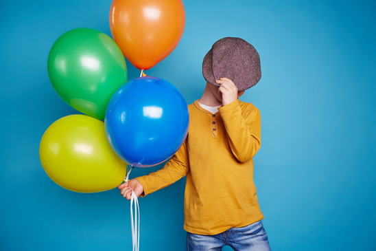 Boy with balloons covering his face with cap