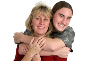 A teenaged boy and his mother posing for a portrait.