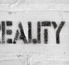 reality word with question mark handwritten on the white brick wall