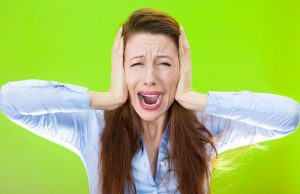 Closeup portrait of worried, stressed, overwhelmed young woman, funny looking girl, covering her ears, screaming going crazy, isolated on green background. Human emotions, facial expressions, reaction
