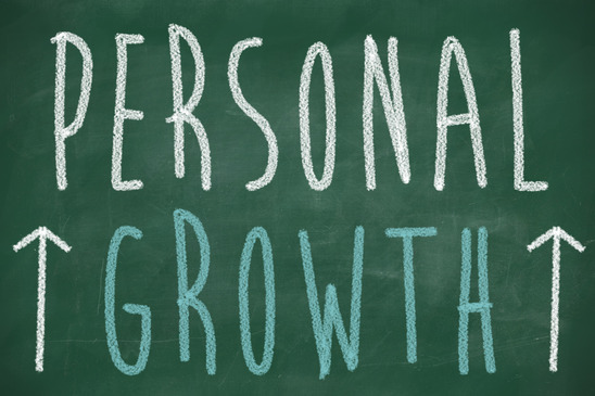 Personal growth phrase handwritten on the chalkboard with rising arrows